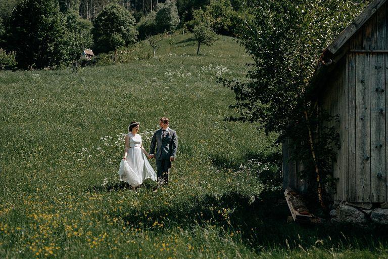 Brautpaar läuft auf einer Wiese