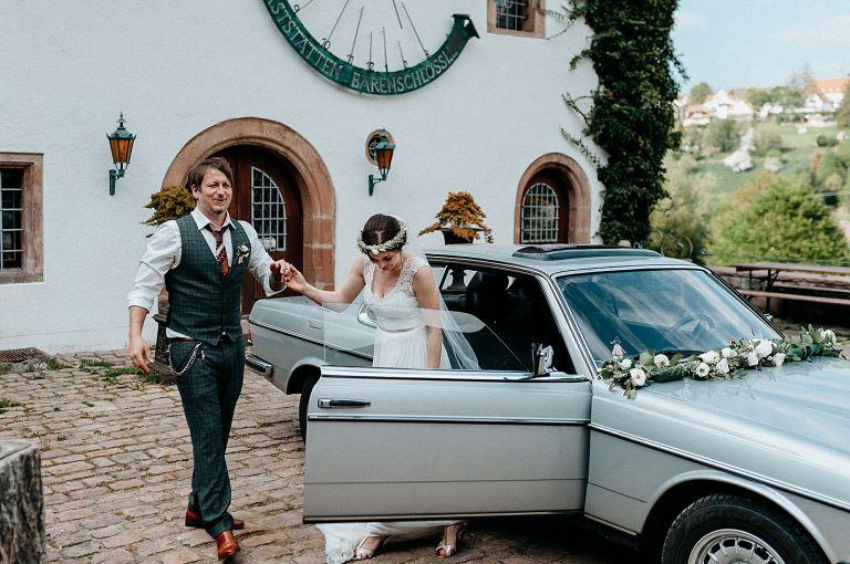 Bräutigam hilft Braut aus dem Auto