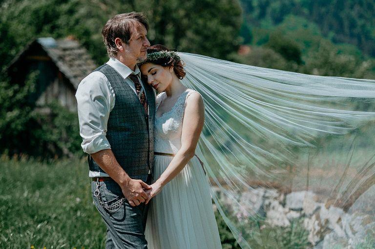 Brautpaar in romantischer Pose, Schleier im Wind