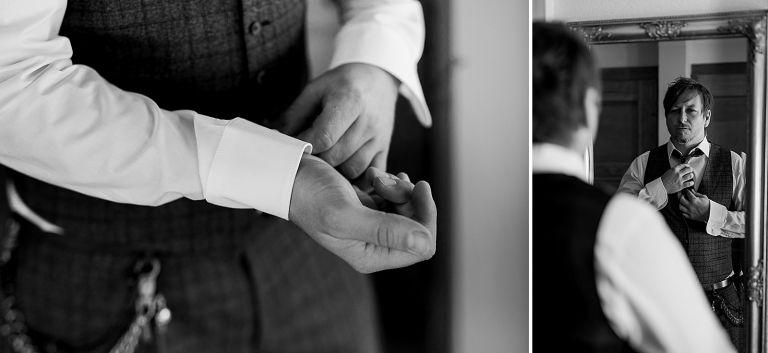 Brautigam steht am Spiegel und zieht sich die Krawatte an