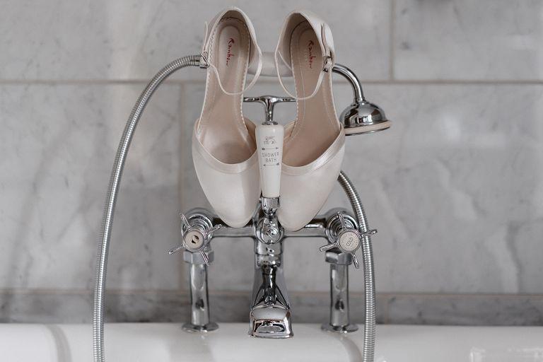 Brautschuhe über Armatur der Badewanne