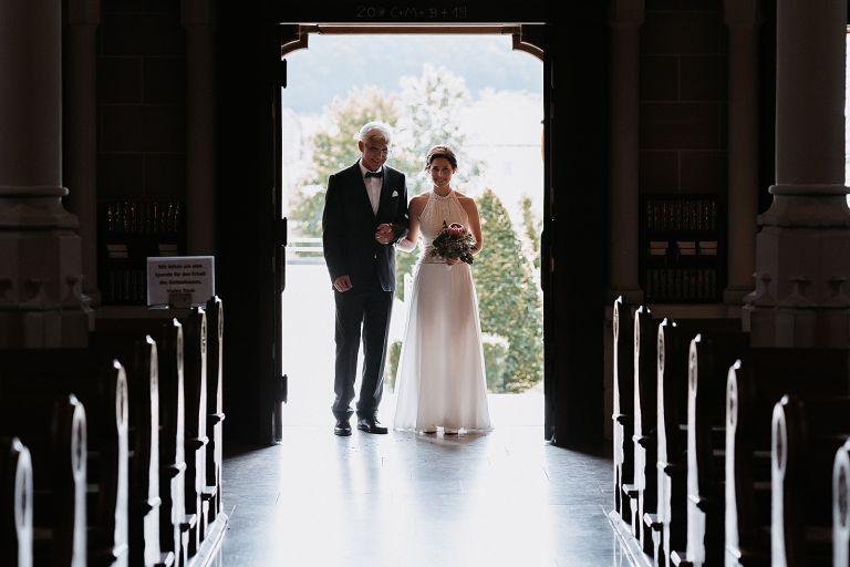 Braut steht mit Brautvater an der Kirchentür
