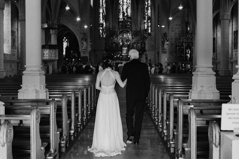 Brautvater mit Braut von hinten wie sie in die Kirche laufen