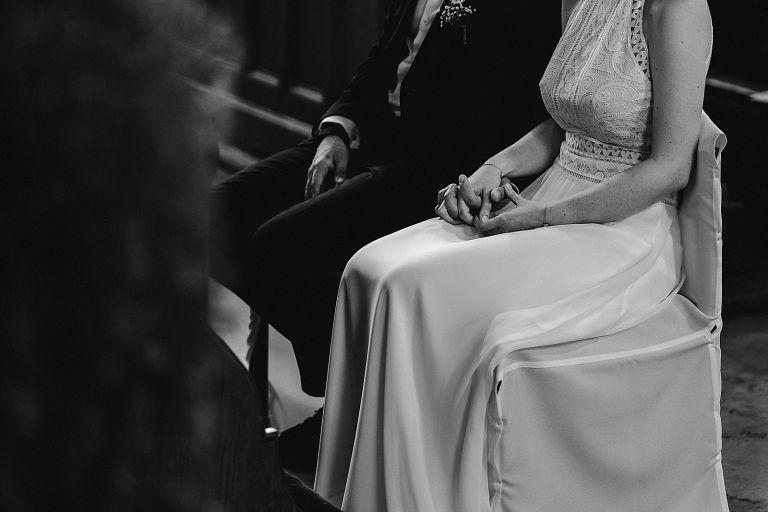 Brautpaar händehaltend sitzend vor dem Altar