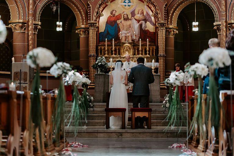 Brautpaar von hinten vor dem Altar