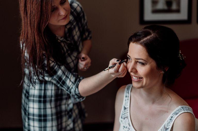 Schwester schminkt die Braut