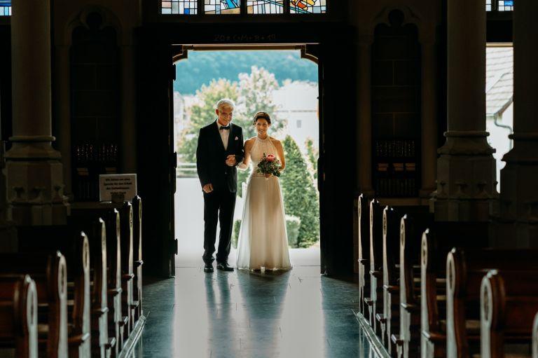 Braut und Vater stehen vor dem Eingang der Kirche
