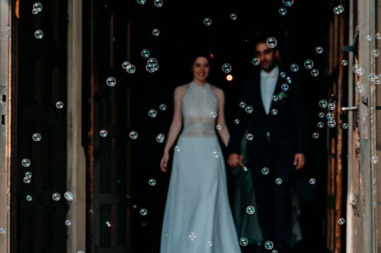 Brautpaar verlässt die Kirche in einem Meer von Seifenblasen