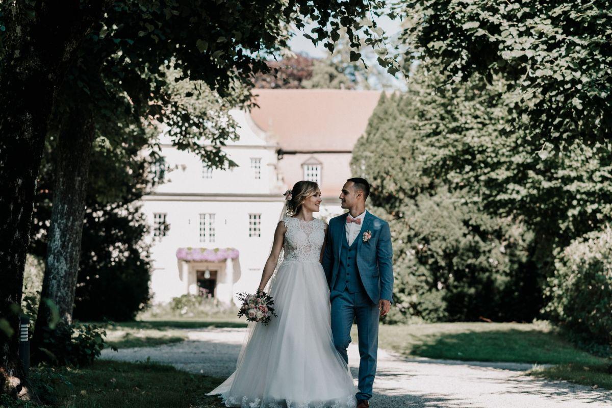Brautpaar läuft Hand in Hand vor dem Schloss